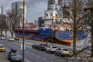 Ein Schiff aus Madeira vor den Hochhaeusern Rotterdams