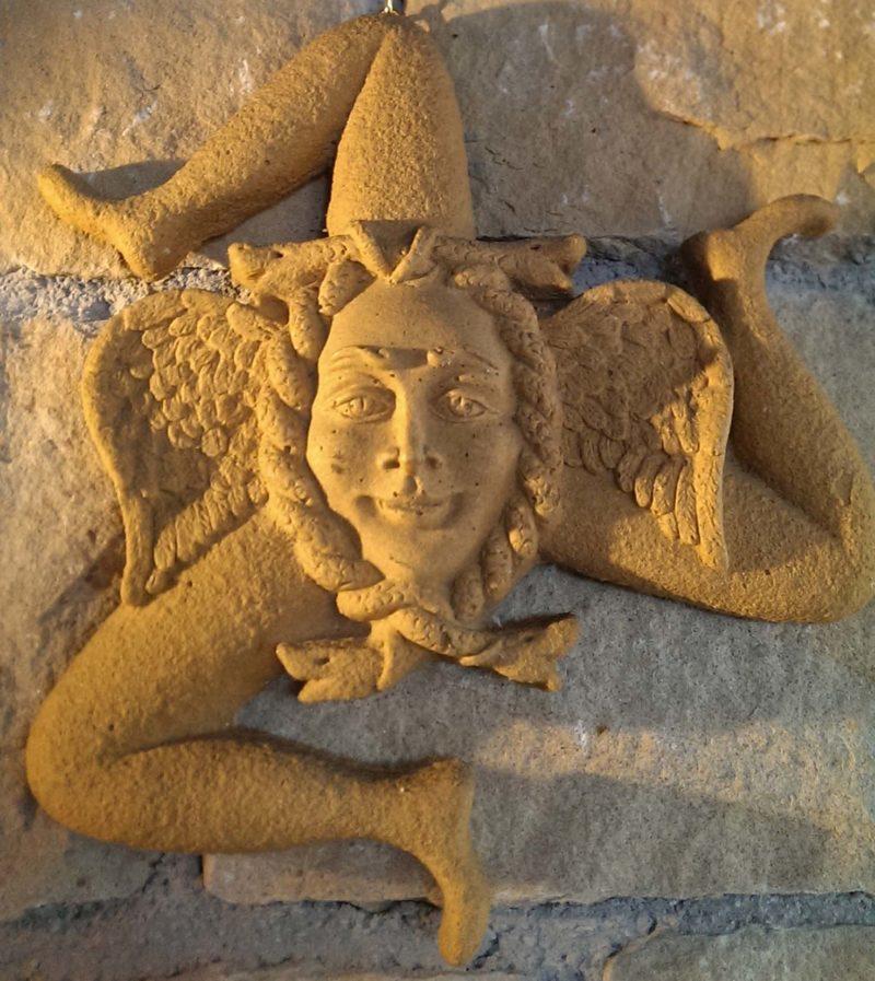 Um einen Mädchenkopf, umrahmt von Schlangen und kleinen Flügeln, laufen drei abgewinkelte Beine: Das uralte Symbol des Sonnenrades erhielt auf Sizilien Gesicht und Namen